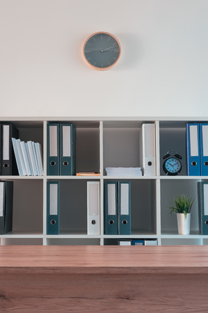 Office shelf with document binders and stationery. Modern workspace interior.