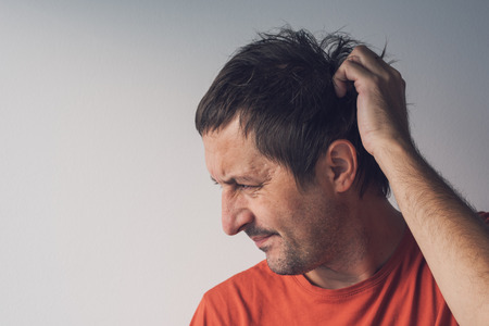 Forgetful absent-minded man is trying to remember something  that he managed to forget.