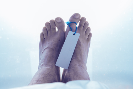 Feet of dead male person in morgue, close up of selective focus Stock Photo