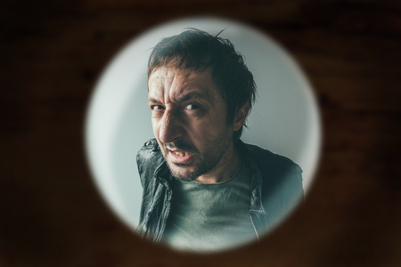 Angry man at the door viewed through spy hole, debt collector or criminal knocking at the door Banque d'images