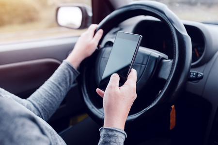 Woman simultaneously driving car and reading text message, mobile smart phone in female hands over vehicle steering wheel