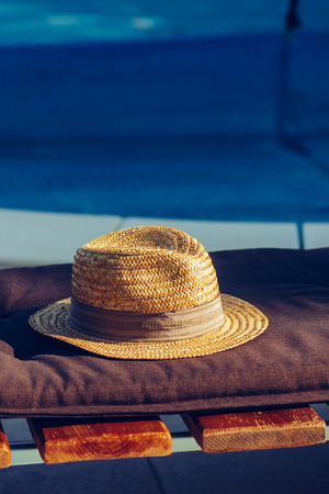 Straw hat on deck chair by the swimming pool in summer morning