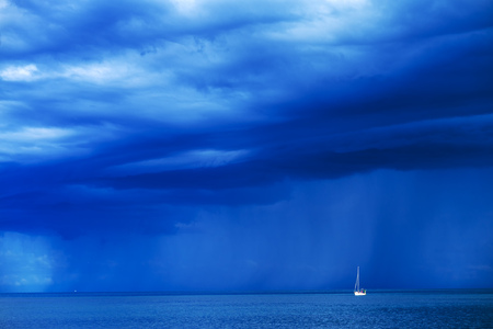 Sailing boat at stormy sea horizon with dark rainy clouds in background Stock Photo