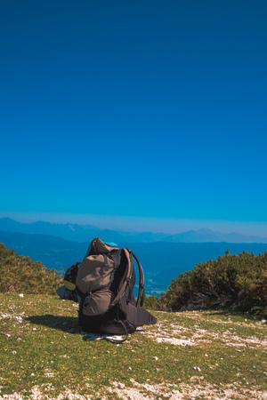 Hiking backpack at top of the mountain on sunny summer day Foto de archivo