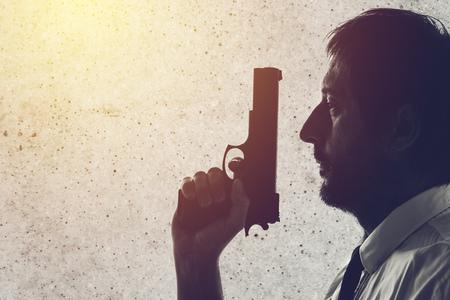 Man with a gun. Police officer, criminal investigation detective or secret service agent. Grunge edit. Stock Photo