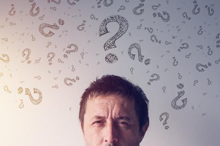 Point d'interrogation, à la recherche de réponses. Un homme perplexe portant des symboles de points d'interrogation griffonnés autour de sa tête. Banque d'images - 91590110