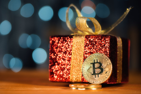 Bitcoin BTC cryptocurrency and Christmas gift box, BTC golden coin as symbol of electronic virtual money for web banking and international network payment Stock Photo