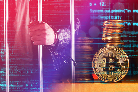 Handcuffed arrested Bitcoin thief in jail, conceptual image