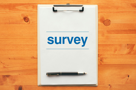Survey questionnaire, overhead view of clipboard note pad on office desk table
