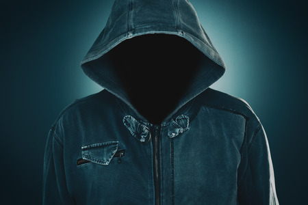 犯罪と暴力の概念のためのパーカー、暗い低キーの肖像画を持つ神秘的な不審な顔のない男