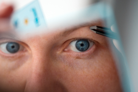 Woman plucking eyebrows with tweezers by the window, selective focus Stockfoto