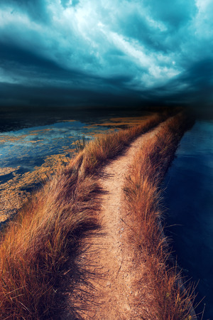 Uncertainty, doubt and insecurity in the future. Risky footpath road through water vanishing in distance, dark stormy moody clouds bringing bad weather coming towards. Banque d'images