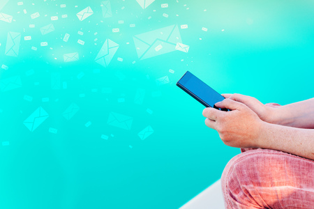 Woman send bulk messages from her smartphone from summer vacation resort poolside 写真素材