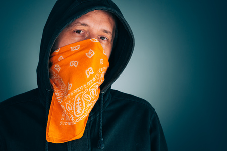 Portrait of masked criminal male person looking at camera. Adult man with hoodie and scarf over face as bandit or gang member.