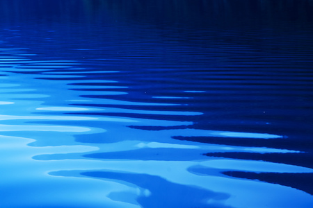 Blue rippled water as abstract background. Tranquil surface texture of the lake. Stock Photo