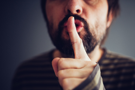 Man saying hush or be quiet with finger on lips, close up with selective focus