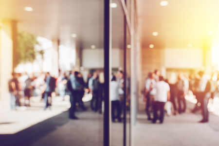 Abstract blur business and entrepreneurship background, unrecognizable crowd of businesepeople in front of corporate premises Stock Photo