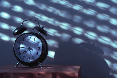 Alarm clock on night table in bedroom ticking time in early morning with sunlight and shadows on the wall in background Stock Photo