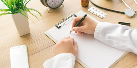 Female doctor writing notes, patient's medical history or medicine prescription on clipboard paper during medical exam in hospital office Standard-Bild