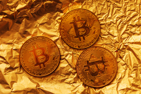 Bitcoin, blockchain cryptocurrency golden coin on gold metal background to emphasize the value of virtual currency in modern world Reklamní fotografie