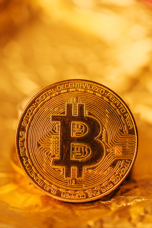 Bitcoin, blockchain cryptocurrency golden coin on gold metal background to emphasize the value of virtual currency in modern world 版權商用圖片