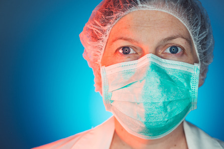 Female surgeon face portrait, adult caucasian woman in healthcare medical protective clothes looking at camera