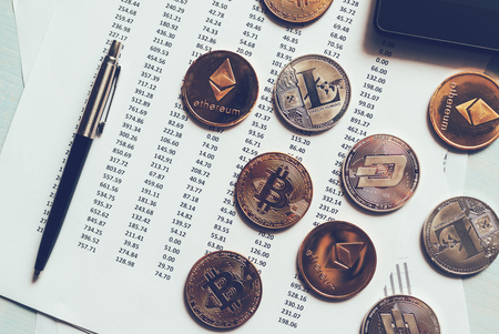 Cryptocurrency coins with exchange rate table, various crypto money on business office dek 写真素材