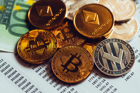 Cryptocurrency coins with exchange rate table, various crypto money with traditional Euro currency banknotes on business office desk