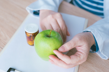 Doctor advising apple instead of pills and antibiotics, female hands in white coat with green fruit as favorable way to achieve and maintain healthy lifestyle