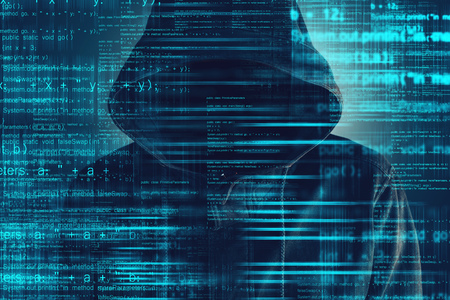 Cybersecurity, computer hacker with hoodie and obscured face, computer code overlaying image Reklamní fotografie