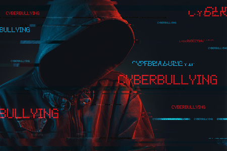 Cyberbullying concept with faceless hooded male person, low key red and blue lit image and digital glitch effect