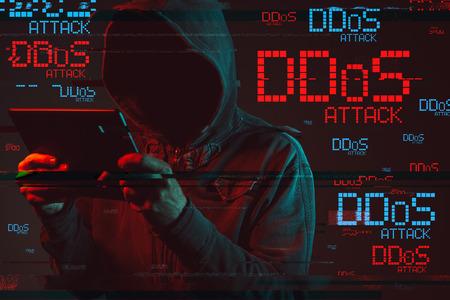 Verteiltes Denial-of-Service- oder DDoS-Angriffskonzept mit gesichtsloser mit Kapuze männlicher Person, die Tablet-Computer, zurückhaltendes rotes und blau beleuchtetes Bild und digitalen Störschubeffekt verwendet
