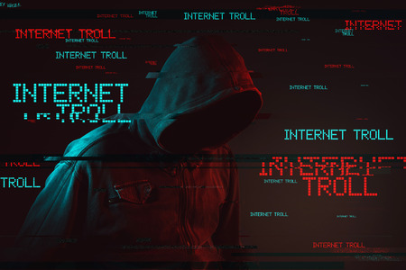Internet troll concept with faceless hooded male person, low key red and blue lit image and digital glitch effect