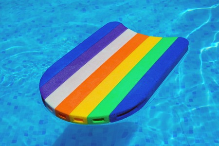 Rainbow pattern swimming board or baseboard floating in swimming pool water, summertime vacation recreational activity object in the poolside