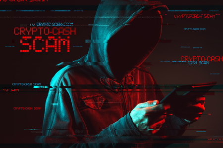 Crypto cash scam concept with faceless hooded male person using tablet computer, low key red and blue lit image and digital glitch effect Stock Photo