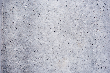 Abstract rough bright concrete surface texture with bugholes as background