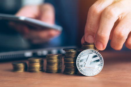 Litecoin cryptocurrency trader, business person using modern technology electronic to trade with crypto money, stacked coins in the foreground and defocussed businessman in background