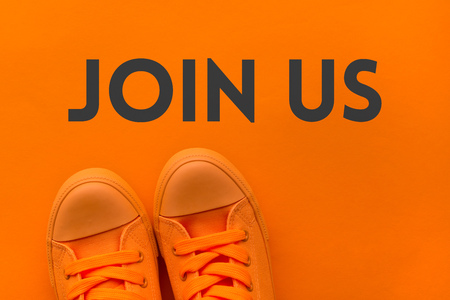 Join us invitation, young person in orange sneakers standing over the text message, top view Stock Photo