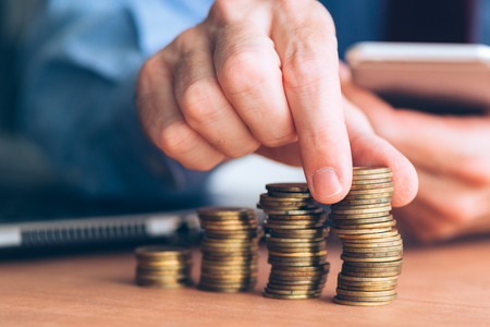 Finances and budgeting, businessman stacking coins on office desk Stock Photo