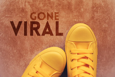 Gone viral concept with top view of yellow sneakers on the pavement