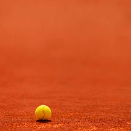 Tennis ball on clay court, selective focus with blank copy space
