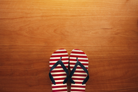 Beach sandals flip flops on wooden background with copy space for summer holiday vacation text message
