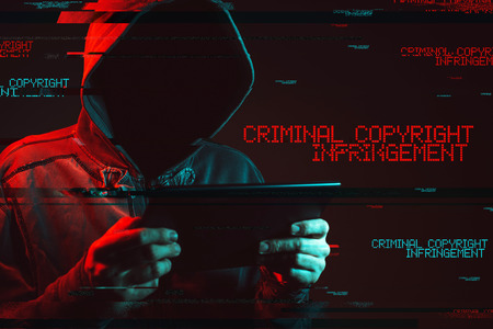 Criminal copyright infringement concept with faceless hooded male person, low key red and blue lit image and digital glitch effect 写真素材
