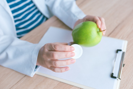 Doctor advising apple instead of pills and antibiotics, female hand in white coat holding green fruit as favorable way to achieve and maintain healthy lifestyle Stock Photo
