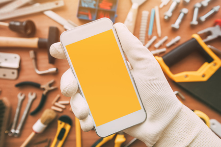 Handyman smart phone app with blank screen. Repairman holding telephone in hand. Copy space for text or maintenance work application or business service, top view Stock Photo