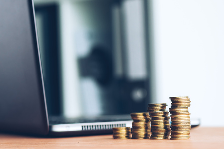 Stacked columns of money coins and laptop computer defocussed in background for finance, economy and budgeting concept Stock Photo
