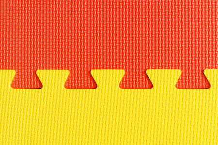 Red and yellow interlocking rubber foam flooring for babies and children indoor activity, top view