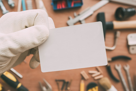 MAintenance worker blank business card as copy space over workshop table with maintenance and fix-up project tools