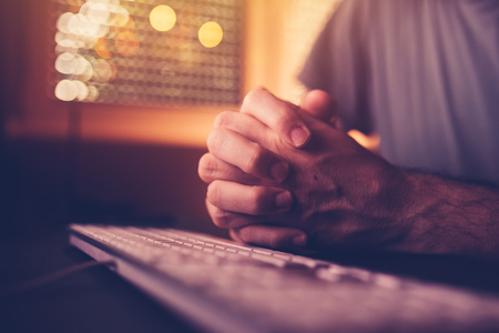 Pray over computer keyboard. Male hands clenched or clasped in praying position in home office interior, low key with selective focus