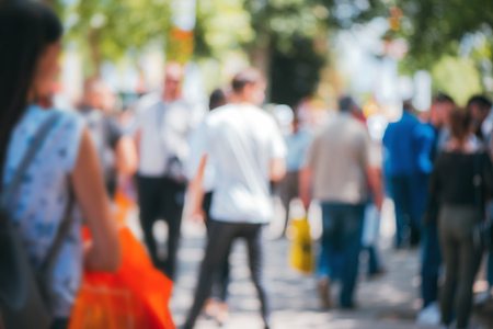 Abstract blurry background, people walking on crowded street on sunny summer day. Defocus blurred background as graphic design element.